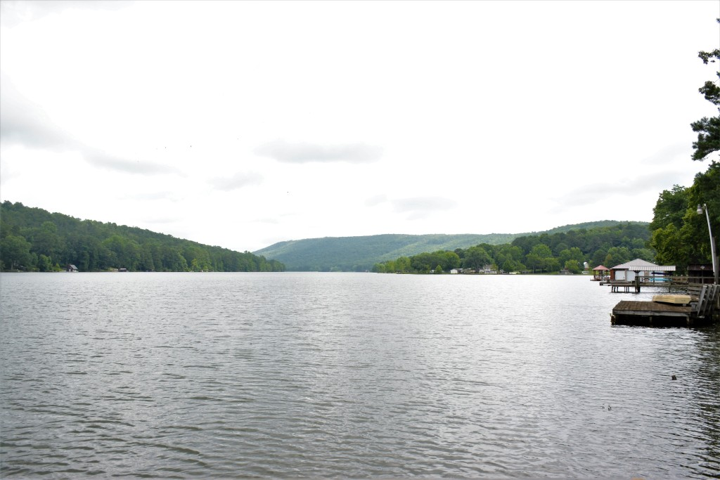 A lake with several small docks and homes visible around its shoreline, surrounded by forested hills.
