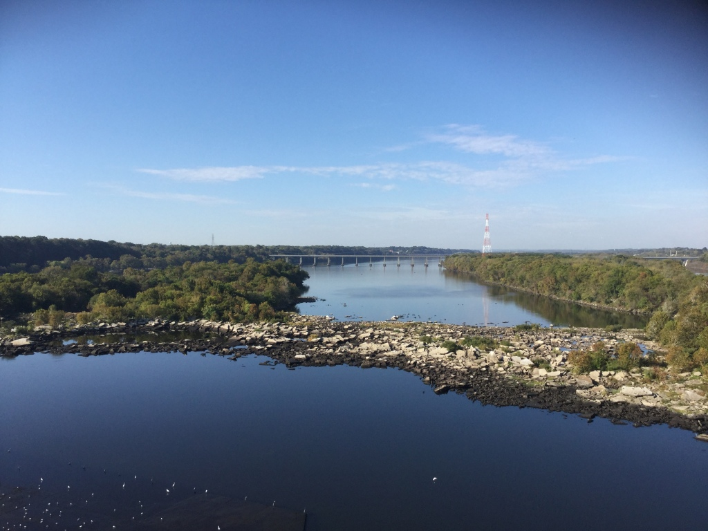 A wide shot of the Tennessee River taken from above, with woodland areas and a bridge visible in the background.