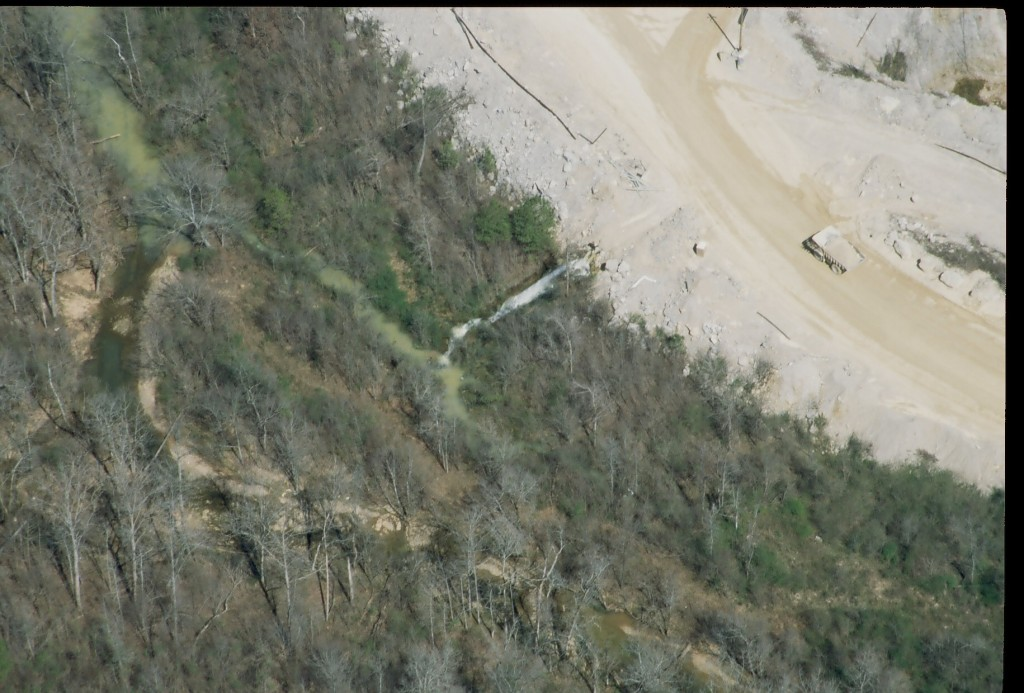 An aerial image showing the quarry site, including a large truck, in the upper right and a wooded area and small creek on the left. The outflow pipe in the center can be seen emitting discharge, and the creek is visibly cloudy.