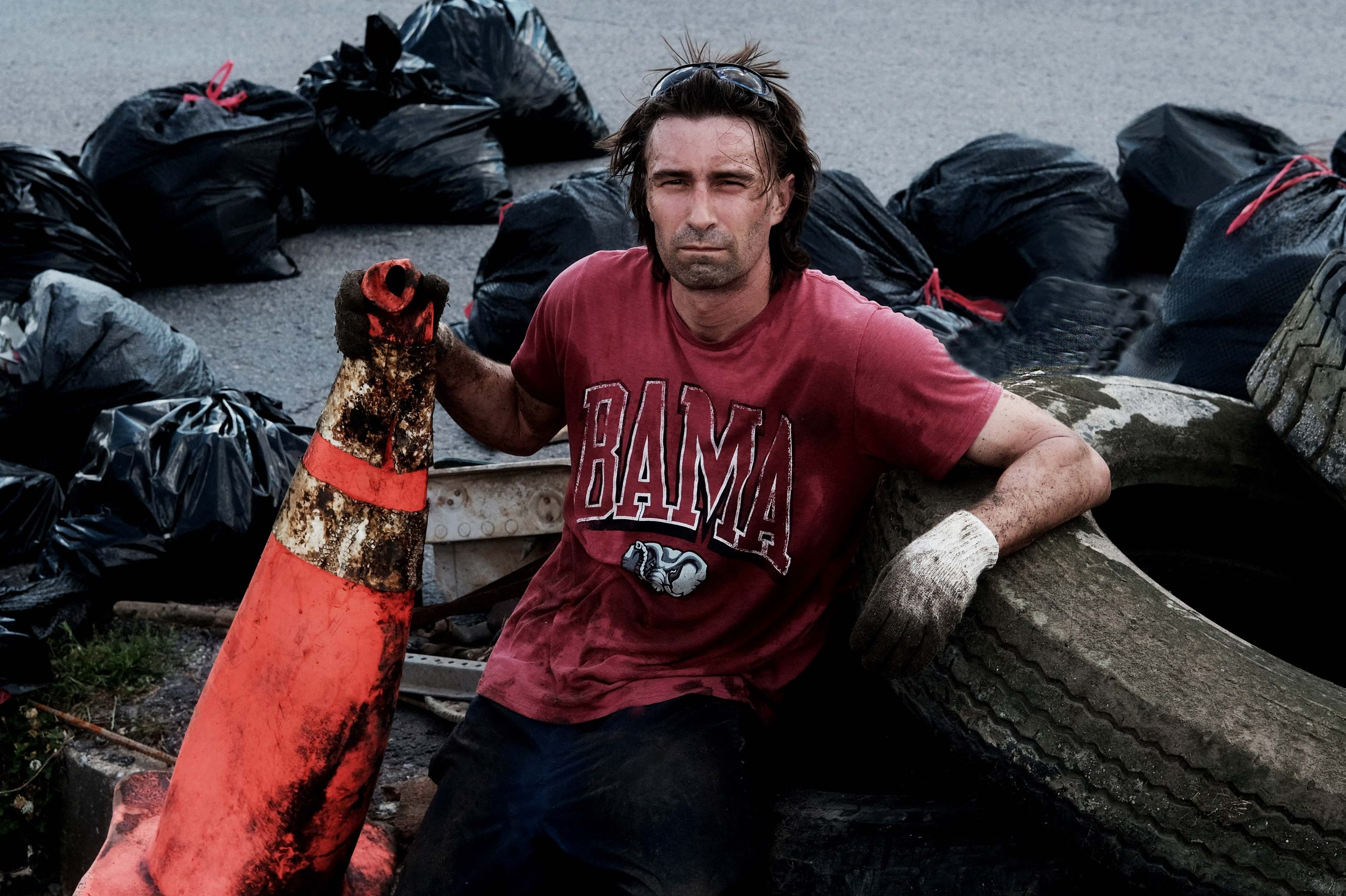 David Whiteside sits among garbage bags of collected litter, along with tires and a traffic cone, during a river cleanup.