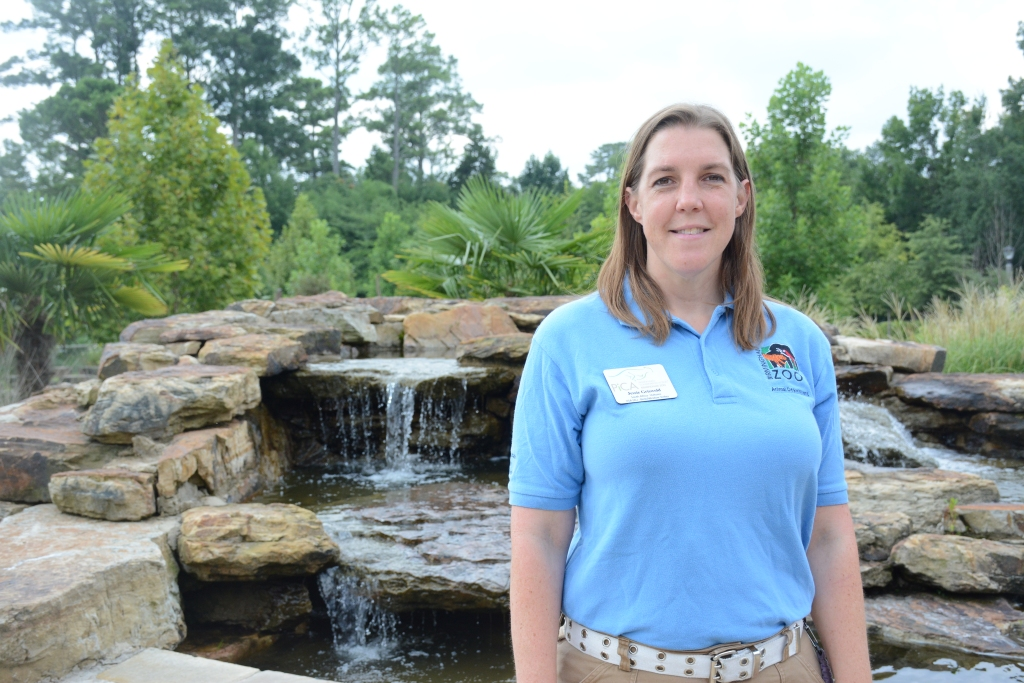 Jessie Griswold stands in front of the waterfall at the Birmingham Zoo entrance.