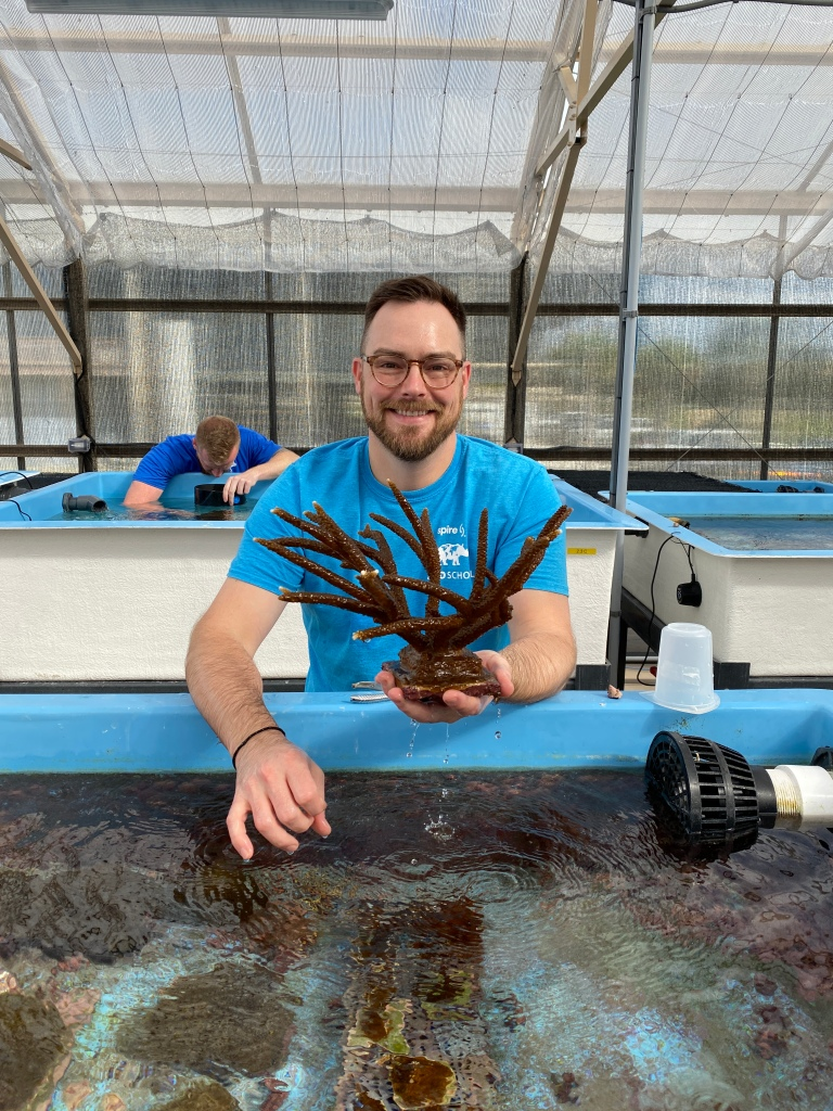 Jesse Daniels holds a large, brown coral. In front of him is a pool with other growing corals visible.