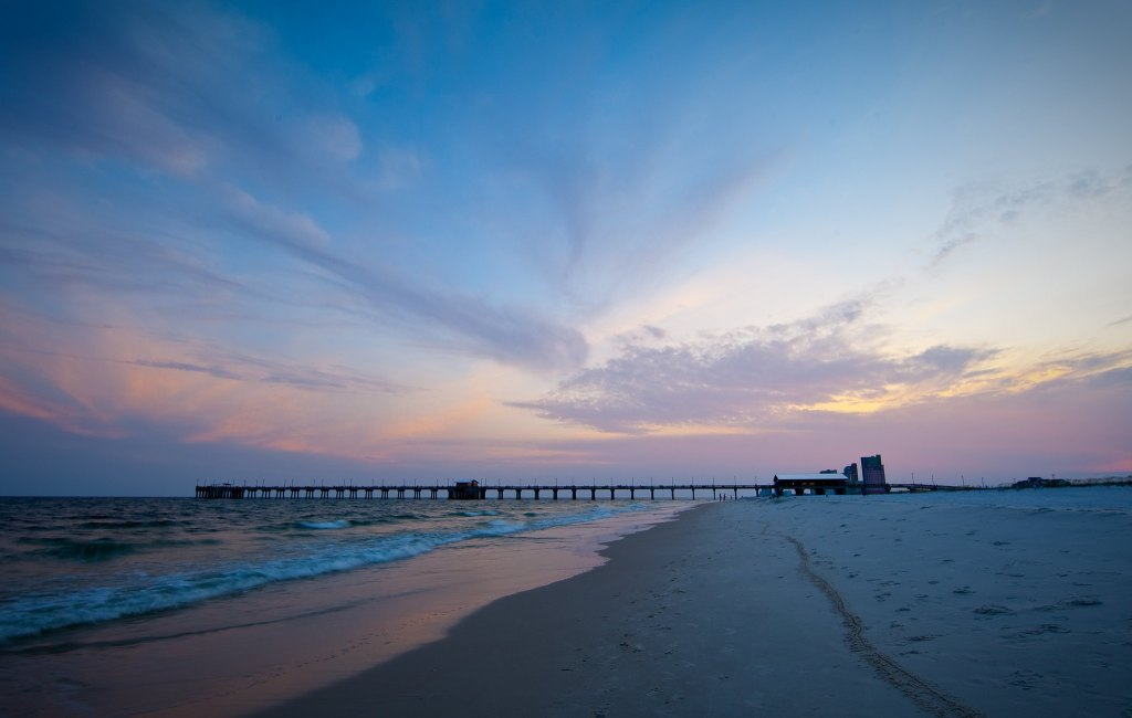 The beach at sunset, with a tall pier and hotels visible in the distance.