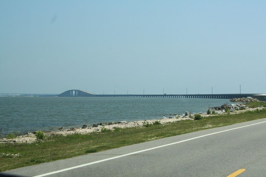 Photo is taken from the road that connects Dauphin Island to mainland Alabama. The Gulf waters can be seen just a few feet from the edge of the road, and the water level is barely lower than the ground the road is built on. In the background, the elevated portion of the causeway, including the bridge to allow ship traffic, can be seen.