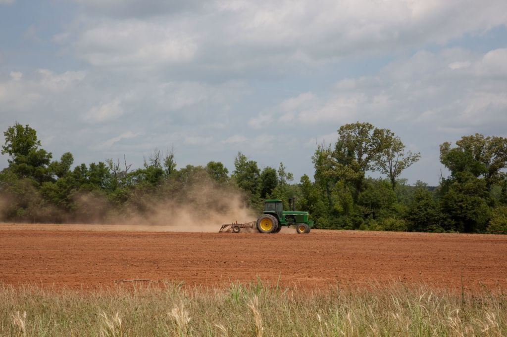 A tractor drives across a dirt field with tilling equipment, raising a plume of dust.