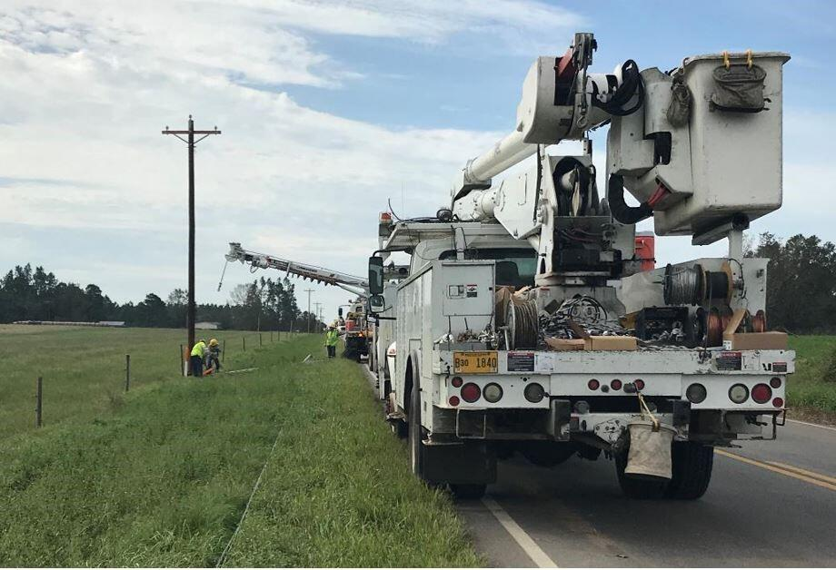 Several power trucks are stopped on the side of a two-lane, rural road. Two workers can be seen working near a power pole, while another worker stands near one of the trucks.