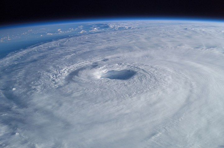 A hurricane seen from space, with the eye visible from the center and the curve of the Earth above the hurricane.